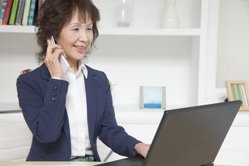 ノートパソコンを使いながら電話するビジネスウーマン