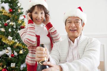 シャンパンをあけるシニア男性と耳を塞ぐシニア女性