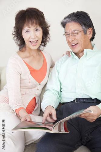 雑誌を読む笑顔のシニアカップル
