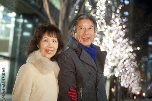 イルミネーションを眺める笑顔のシニアカップル