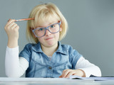 Blonde girl with glasses is concentrated doing her homework