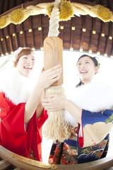笑顔でお参りをする振袖姿の女性2人