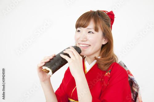 恵方薪を食べる振袖姿の女性