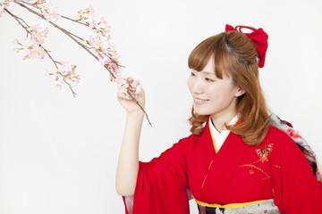 桜を見る振袖姿の女性