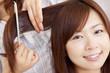 美容師に髪を梳かしてもらう女性