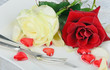 Romantic place setting with darkred and white rose and hearts