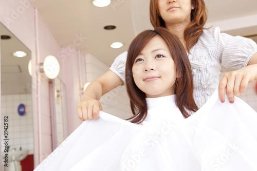 美容師にカットクロスをつけてもらう女性