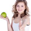 Junge Dame mit grünem Apfel hält Daumen hoch