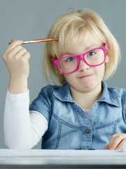 Blonde girl with pink glasses thinking about difficult exercises