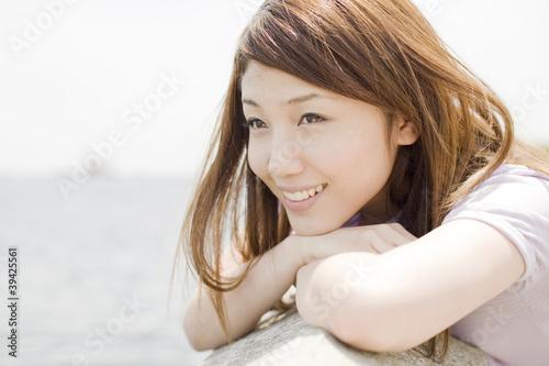 堤防で海を眺める笑顔の女性