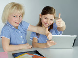 Girls shows thumbs up for learning by mobile device