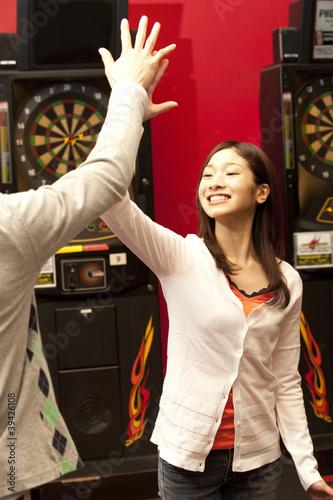 ダーツゲームをしてハイタッチする男女