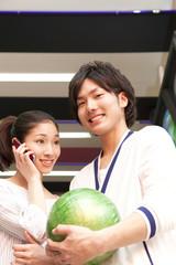 ボウリング球を持つ男性とスマートフォンで話す女性