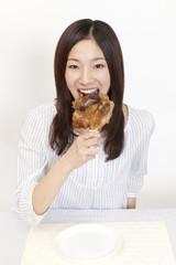 骨付き肉を食べる女性