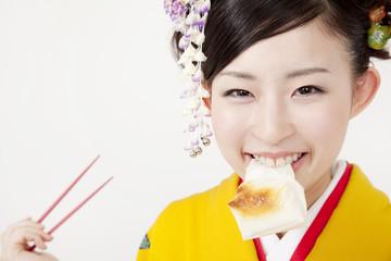 餅を食べる振袖姿の女性