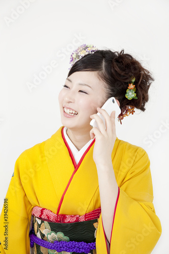 スマートフォンで電話をする振袖姿の女性