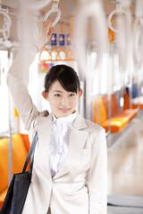 電車内でつり革につかまる笑顔のOL