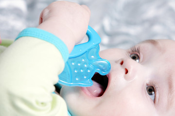 Cute baby with a blue fish teether