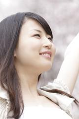 桜の下で伸びをする笑顔の女性