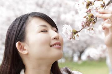 桜の香りを嗅ぎ微笑む女性