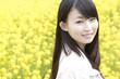菜の花畑で振り返り微笑む女性