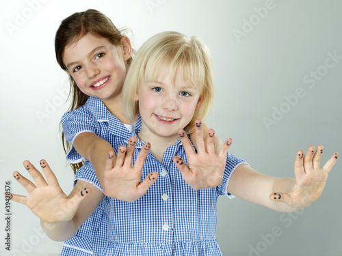 Cute girlfriends with painted fingers having fun