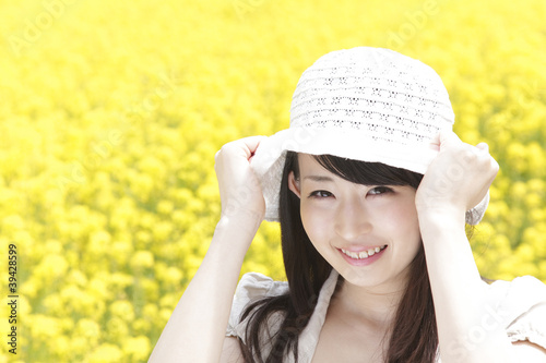 菜の花畑で帽子を被り微笑む女性