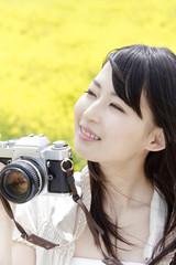 菜の花畑でカメラを持つ笑顔の女性