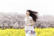 菜の花畑を走る笑顔の女性