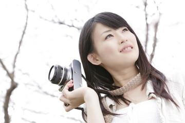 桜の下でカメラを持つ笑顔の女性