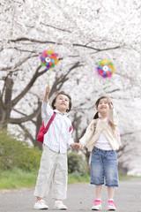 桜の下で風車を持つ男の子と女の子