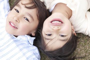 芝生に寝転がり微笑む男の子と女の子