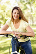 Hispanic woman in park with bike