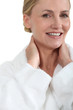 Woman in bath robe smiling with hands behind neck
