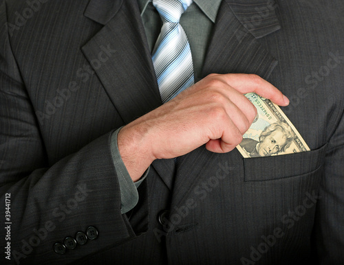 Businessman putting a dollar bill in his pocket stock image
