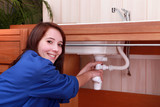 Young woman plumbing a sink