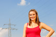 Frau steht vor einem Strommast