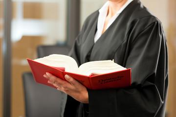 Anwältin mit Gesetzbuch und Robe