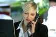 Blond office worker using land-line telephone