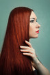 young woman with elegant long red shiny hair.