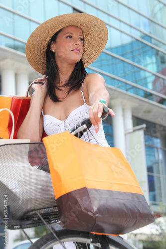 Summer in the city: woman with shopping bags and bicycle
