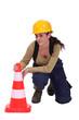 Woman kneeling by traffic cones