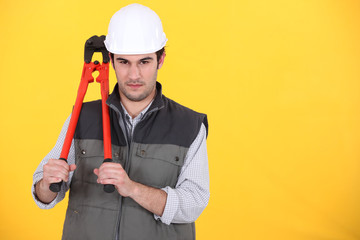 portrait of craftsman holding spanner against yellow background
