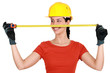 Tradeswoman extending a measuring tape