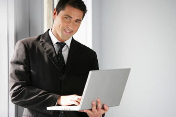 Man stood in office holding laptop