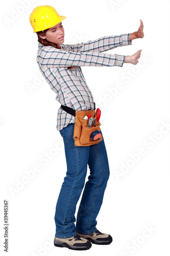 Tradeswoman pushing up against an invisible wall