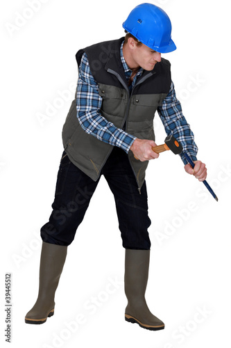 Laborer using hammer on white background