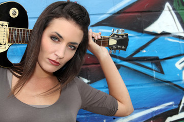 Female guitarist standing in front of a graffitied wall