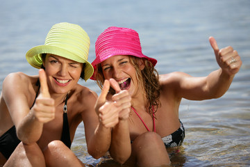 Two women at the beach giving the thumbs-up