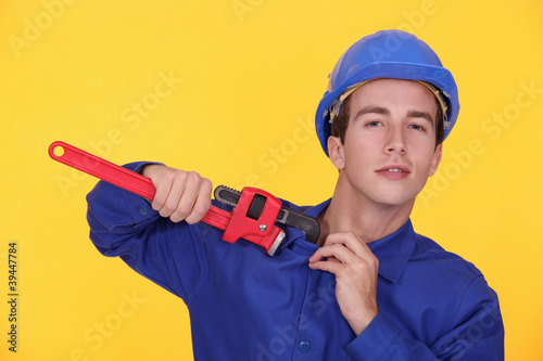 young plumber holding adjustable spanner